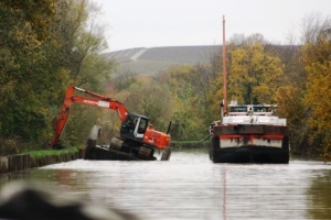 The skilful skipper of the dredge operator in action as he moves his excavator platform and then the barge so we can pass.